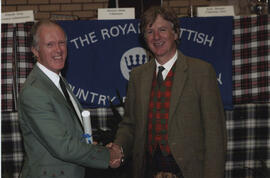 Photograph of Bruce Frazer receiving a scroll from the Hon. Peregrine of Moncrieffe