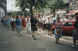 "Photograph of people taking part in ""Piping"" in the Streets. Jim Rae leading, playing the pipes"