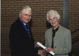 Photograph of Margaret Spouse receiving a scroll from Lord Mansfield at the AGM, 2004