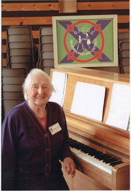 Photograph of Jean Sim, sitting at a piano