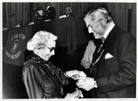 Photograph of Helene Jensen with Lord Mansfield receiving a scroll from Lord Mansfield at the AGM, 1988