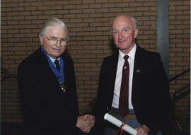 Photograph of Joe Murphy receiving a scroll awarded postumously to Alice Murphy from Lord Mansfield at the AGM in 2004