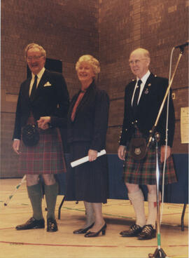 Photograph of Betty and David Grant recieving a scroll from Bill Clement