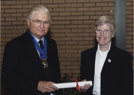 Photograph of Christine Traynor rreceiving a scroll from Lord Mansfield at the AGM, 2004