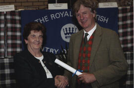 Photograph of Jessie Harper receiving a scroll from the Hion
