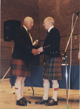 Photograph of Ian Hall receiving a scroll from Bill Clement