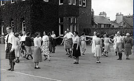 Photograph of a group dancing in mixed sets, taken outside