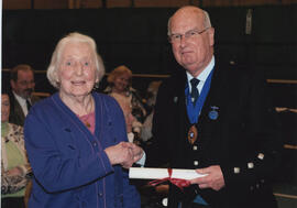 Photograph of Jean Sim  being presented with a Scroll by Alastair MacFadyen at the AGM, 2009