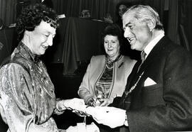 Photograph of Margaret MacWaters and Joan Moore receiving a scroll from Lord Mansfield at the AGM, 1988