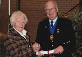 Photograph of Barbara Peel being presented with a Scroll by Alastair MacFadyen at the AGM, 2009