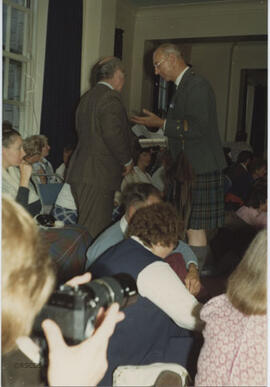 Photograph of Group Captain David Huxley - holding the ceilidh umbrella - talking to John Brodie