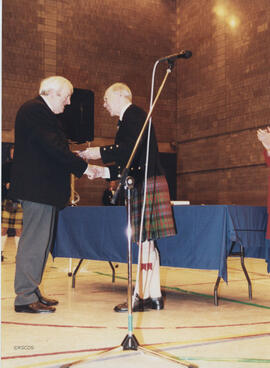 Photograph of John Drewry recieving a scroll from Bill Clement