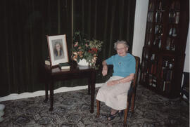 Photograph of Florence Adams with a portrait and selection of pot plants presented by Glasgow Bra...
