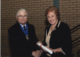 Photograph of Georgina Finlay receiving a scroll from Lord Mansfield at the AGM, 2004