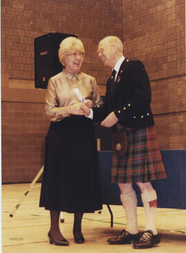 Photograph of Elma See receiving a scroll from Bill Clement