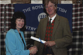 Photograph of Johan Maclean receiving a scroll from the Hon. Peregrine of Moncrieffe