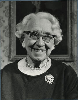 Photograph of Jean Milligan with her portrait in the background