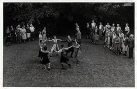 Photograph of a group of dancers dancing a circle