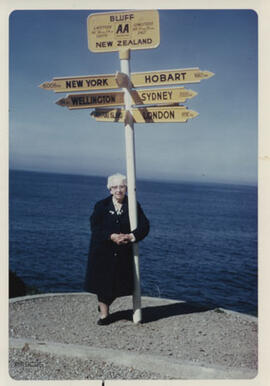 Photograph of Jean Milligan in New Zealand beside a sign-post pointing to New York, Wellington, Hobart, Sydney & London