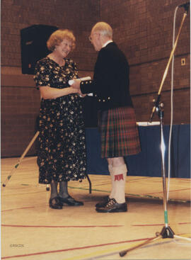 Photograph of Noreen MacLennon receiving a scroll from Bill Clement at the AGM, 1999