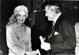 Photograph of Margaret Parker receiving a scroll from Lord Mansfield at the AGM, 1988