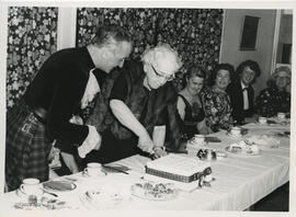 Photograph of Jean Milligan cutting a cake at a joint celebration of Castle Douglas, Gatehouse of...