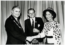 Photograph of Muriel Gibson being presented with keys to a car and a broach ion her retirement. Lord Mansfield, Alastair Aitkenhead and Muriel Gibson